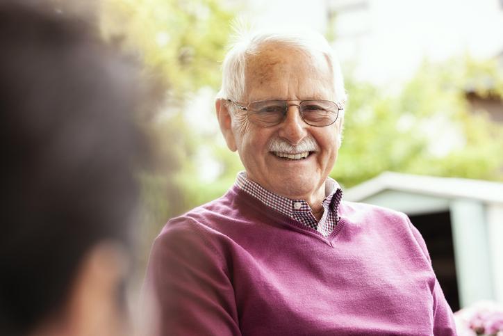 smart older man sat in the garden