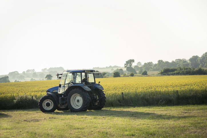 Idyllic British farming scene of a tractor in a field of Rapeseed in the Peak District National Park.