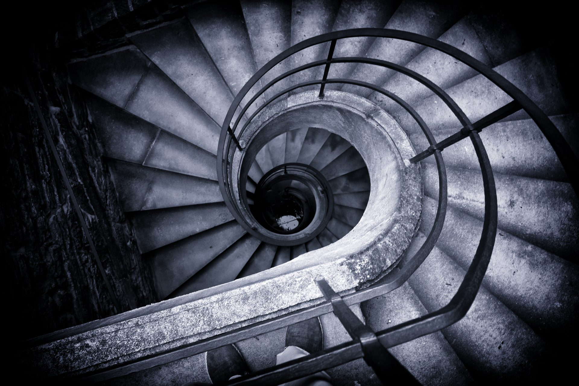 black-and-white-high-angle-view-of-spiral-staircase-winding-down