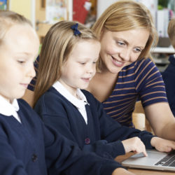Teacher Helping Female Elementary School Pupils In Computer Class